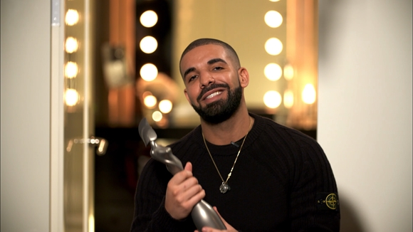 Drake accepting his trophy for International Male