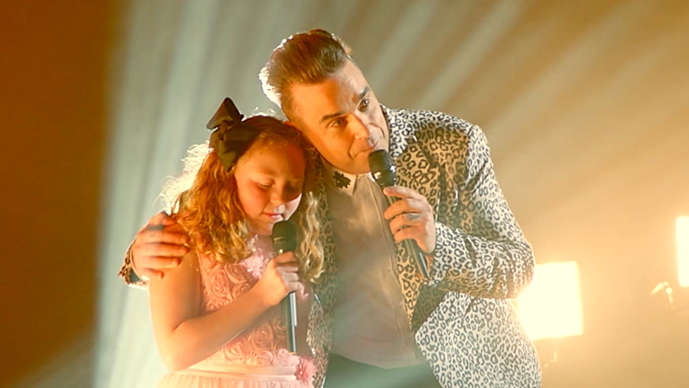 Robbie Williams duets with fans daughter for Priceless Surprise